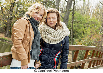 Portrait of two beautiful women in autumn park
