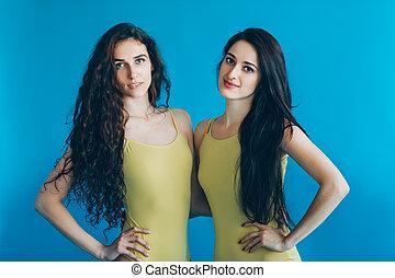 Portrait of two beautiful women on blue background