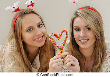 portrait of two beautiful young girls doing sweet heart with Christmas candys
