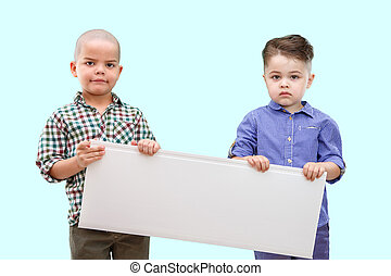 Portrait of two boys holding white sign on isolated background