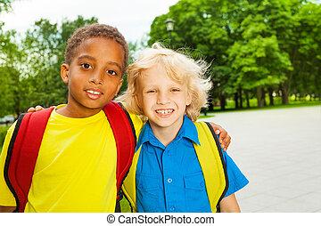 Portrait of two boys hugging on shoulders