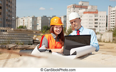 Portrait of two builders  at building site