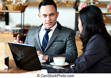 two business people meeting at coffee shop - portrait of two...