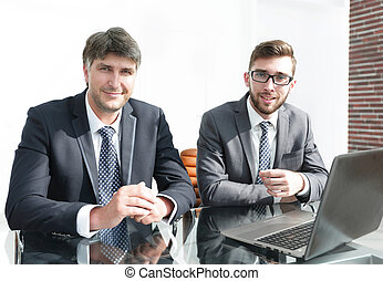 Portrait of two business people sitting at office desk