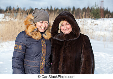Portrait of two Caucasian cheerful women in warm clothing outdoor