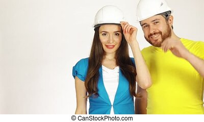 Portrait of two cheerful engineers or architects wearing had hats against white background. 4K clip