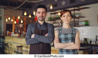 Portrait of two cheerful waiters standing inside cozy cafe,...