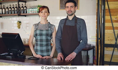 Portrait of two confident waiters in aprons standing at...