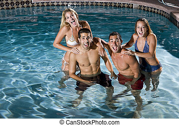 Portrait of two couples in swimming pool at night