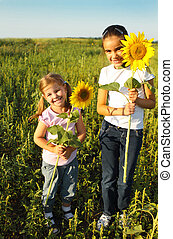 Portrait of two cute litle girls with sunflowers