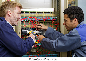 portrait of two electricians measuring voltage