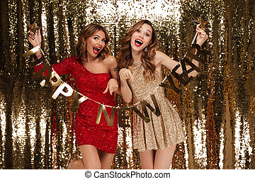 Portrait of two excited attractive women in sparkly dresses