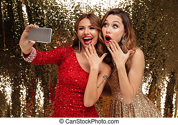 Portrait of two excited cheerful women in sparkly dresses