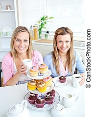 Portrait of two female friends eating pastries and drinking coffee in the kitchen at home