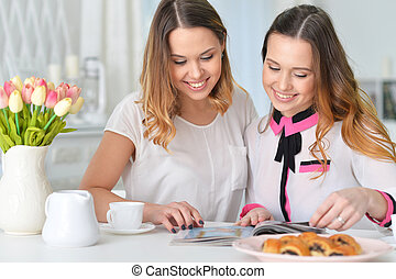Portrait of two female friends looking at magazine