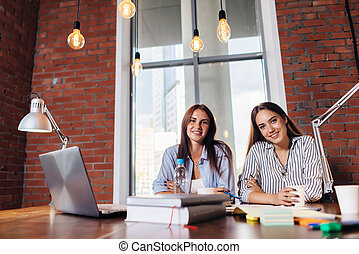 Portrait of two female students smiling, sitting at desk, looking at camera preparing for lessons, doing homework together.