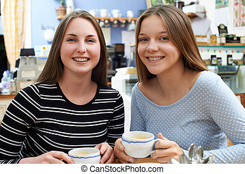 Portrait Of Two Female Teenage Friends Meeting In Cafe