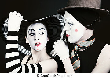Portrait of two flirting mimes on a black background