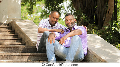 Portrait of homosexual couple hugging outdoor and looking at camera. Same sex marriage between hispanic men. Two happy gay people smiling and posing.