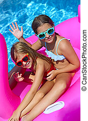 Portrait of two girls wearing sunglasses, happy friends on inflatable flamingo swim float