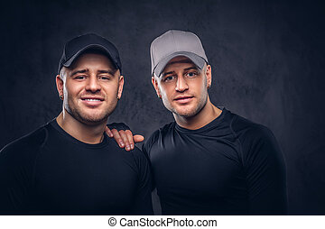 Portrait of two handsome young male dressed in a black sportswea