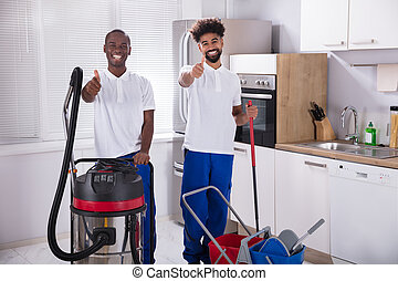 Portrait Of Two Happy Male Janitor In The Kitchen