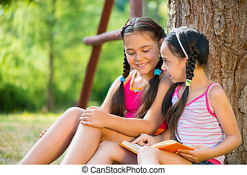 Portrait of two happy sisters reading in the park