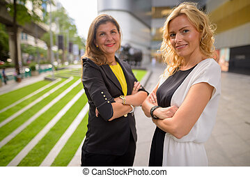 Portrait of two happy woman smiling together outdoors