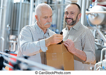 portrait of two joyful smiling workers working on beer factory