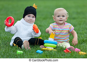 Portrait of two little girls playing on the grass