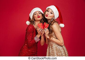Portrait of two lovely cute women in christmas hats