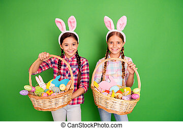 Portrait of two lovely sweet cheerful cheery positive pre-teen girls wearing checked shirt having fun holding in hands festive baskets isolated over bright vivid shine green background