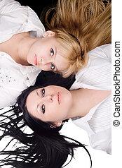 Portrait of two lying beautiful young women