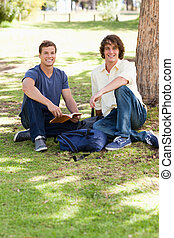 Portrait of two male students studying in a park