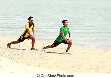 two man exercise on the beach