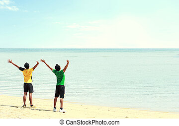 two man raised arm on the beach