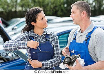 portrait of two mechanics outdoors