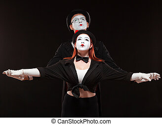 Portrait of two mime artists performing, isolated on black background. Man is standing behind the woman holding her hands.