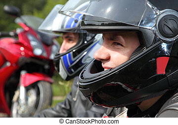 portrait of two motorcyclists sitting on country road near...
