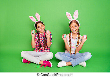 Portrait of two nice sweet lovely cute cheerful cheery pre-teen girls wearing checked shirt sitting crossed legs prepared ready to feast isolated over bright vivid shine green background