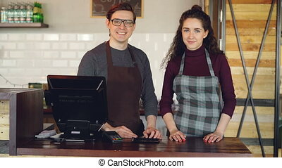 Portrait of two partners small business owners standing at cashier's desk in coffee-house and smiling. Successful business, happy people and food service concept.