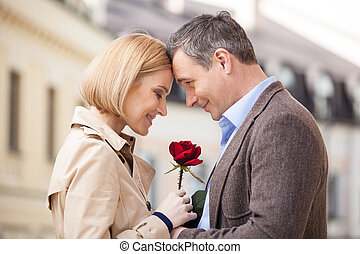 Portrait of two people holding rose and smiling. adult man giving red flower to blond woman outside