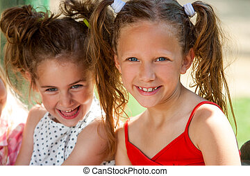 Portrait of two ponytailed girls.