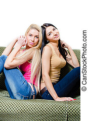 Portrait of two pretty young girlfriends or sisters on sofa