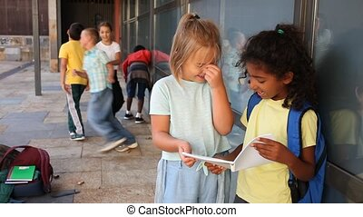 Two girls looking at exercise book talking about homework after classes near school