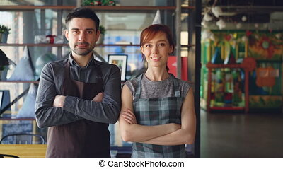 Portrait of two proud small business owners standing inside new spacious cafe and smiling. Successful business start-up, happy people and food service concept.