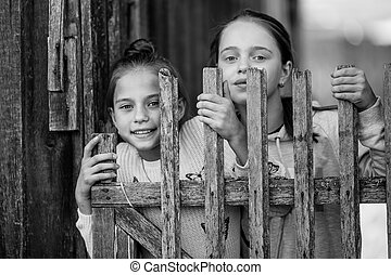 Portrait of two sisters girls teenagers look out from behind a wooden village fence. Black and white photo.