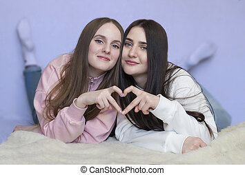 Portrait of two sisters lying on the floor smiling.