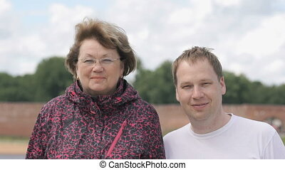 Portrait of two smiling adult woman and young man