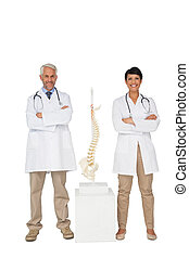 Portrait of two smiling doctors with skeleton model